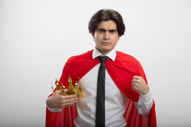 Confiant jeune gars de super-héros regardant la caméra portant une cravate tenant la couronne et le poing