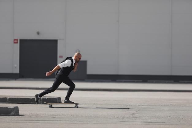 Confiant jeune homme d'affaires en costume d'affaires sur longboard se dépêchant de son bureau