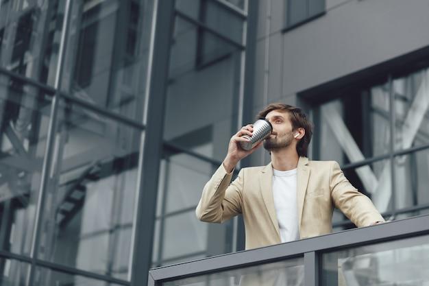 Confiant jeune homme d'affaires en costume élégant, boire du café chaud de la tasse termo tout en se tenant à l'extérieur