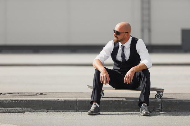 Confiant jeune homme d'affaires à lunettes marchant dans la rue, à l'aide de longboard près d'un bâtiment moderne