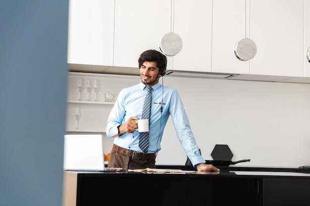 Confiant jeune homme d'affaires travaillant à la maison à la cuisine