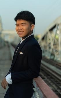 Confiant jeune homme asiatique dans un costume appuyé sur un pont
