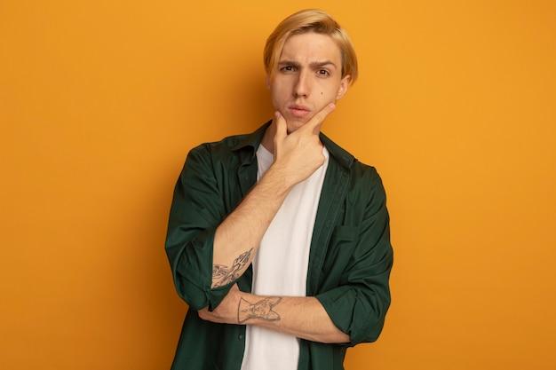 Confiant jeune homme blond vêtu d'un t-shirt vert a attrapé le menton