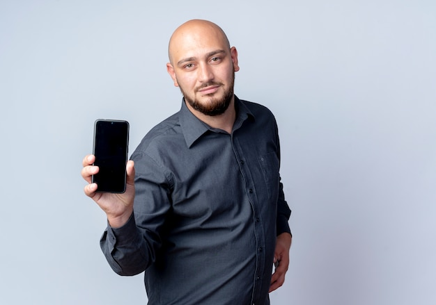 Confiant jeune homme de centre d'appels chauve s'étendant sur le téléphone mobile vers la caméra isolé sur blanc avec copie espace
