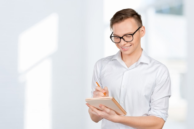 Confiant jeune homme en chemise prendre des notes dans son carnet