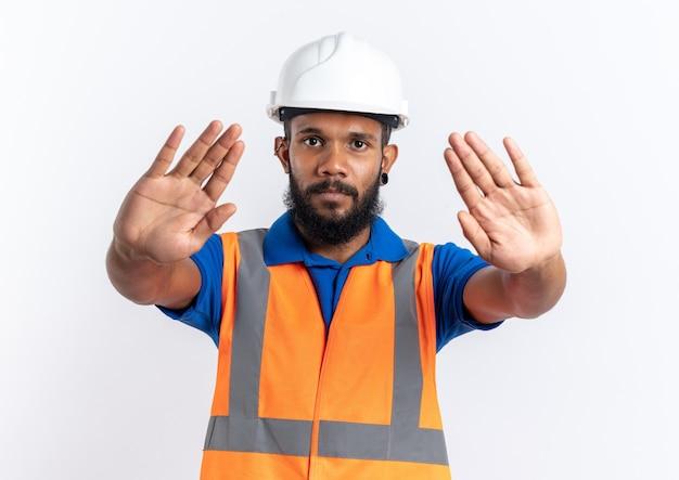 Confiant jeune homme constructeur afro-américain en uniforme avec un casque de sécurité gesticulant un panneau d'arrêt à deux mains isolé sur fond blanc avec espace de copie