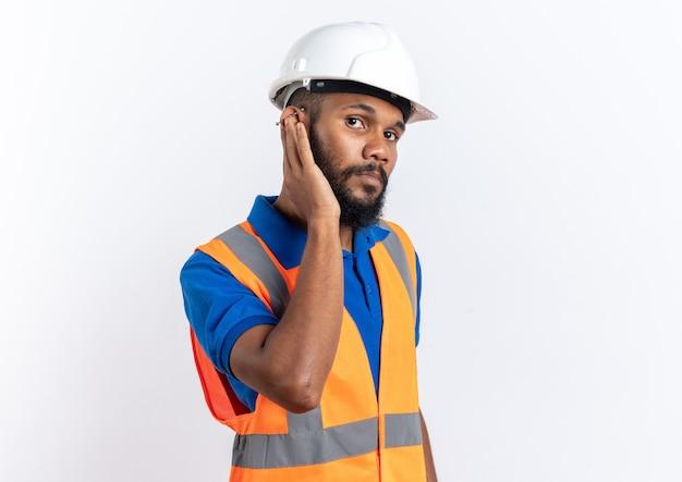 Confiant jeune homme constructeur afro-américain en uniforme avec casque de sécurité mettant sa main sur l'oreille isolé sur fond blanc avec espace de copie