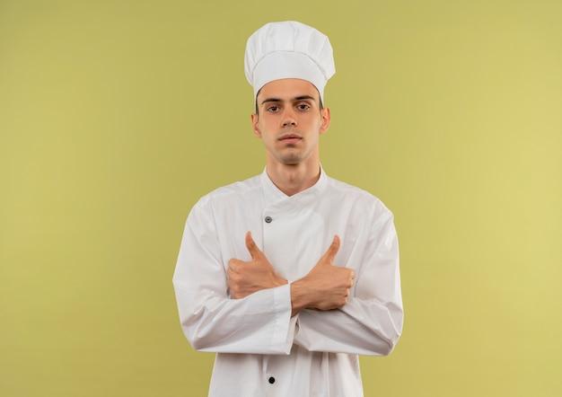 Confiant jeune homme cuisinier portant l'uniforme de chef srossing mains ses pouces vers le haut sur un mur vert isolé avec copie espace