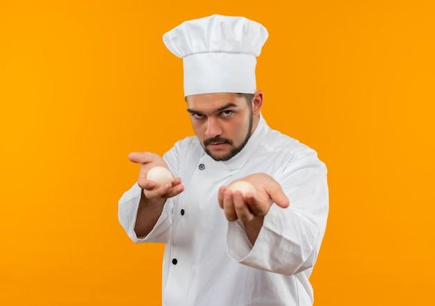 Confiant jeune homme cuisinier en uniforme de chef étirant les œufs vers isolé sur mur orange avec espace de copie