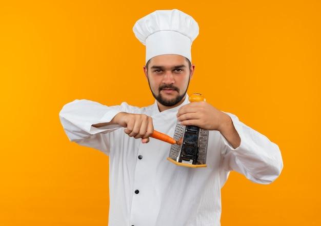 Confiant jeune homme cuisinier en uniforme de chef râper la carotte avec une râpe isolée sur un mur orange