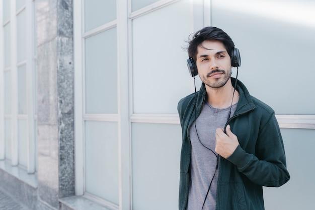 Confiant jeune homme dans les écouteurs sur la rue