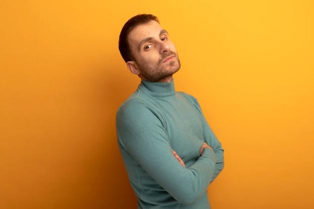 Confiant jeune homme debout avec une posture fermée en vue de profil à l'avant isolé sur mur orange