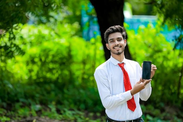 Confiant jeune homme indien montrant son téléphone intelligent