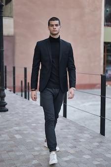 Confiant jeune homme marchant dans une rue de la ville européenne