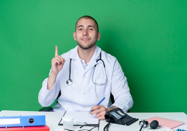 Confiant jeune homme médecin portant une robe médicale et un stéthoscope assis au bureau avec des outils de travail en levant le doigt et tenant un stylo isolé sur vert