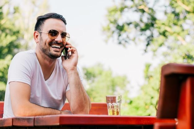 Confiant jeune homme parlant au téléphone mobile et souriant assis au café.