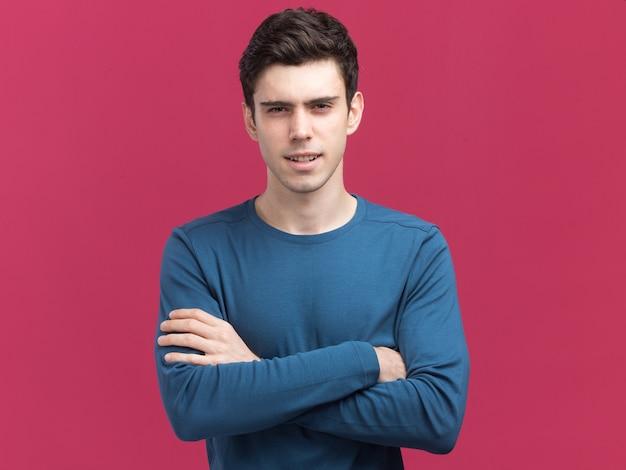 Confiant jeune homme de race blanche brune se tient les bras croisés isolés sur le mur rose avec espace de copie