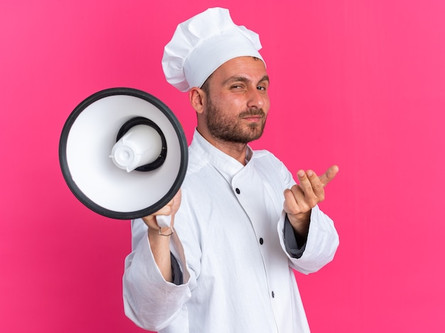 Confiant jeune homme de race blanche cuisinier en uniforme de chef et casquette debout dans la vue de profil tenant le haut-parleur regardant la caméra en train de venir ici geste isolé sur mur rose