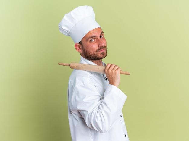 Confiant jeune homme de race blanche cuisinier en uniforme de chef et casquette debout en vue de profil tenant un rouleau à pâtisserie sur l'épaule