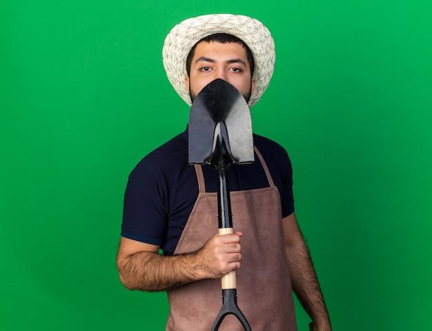 Confiant jeune homme de race blanche jardinier wearing gardening hat holding spade isolé sur mur vert avec copie espace