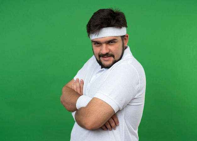 Confiant jeune homme sportif portant un bandeau et un bracelet croisant les mains isolés sur le mur vert