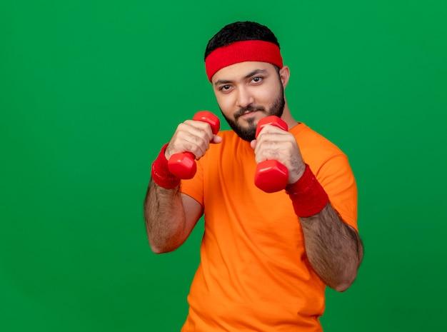 Confiant jeune homme sportif portant bandeau et bracelet debout dans la posture de combat