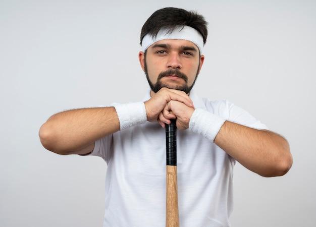 Confiant jeune homme sportif portant un bandeau et un bracelet mettant le menton sur une batte de baseball isolé sur un mur blanc