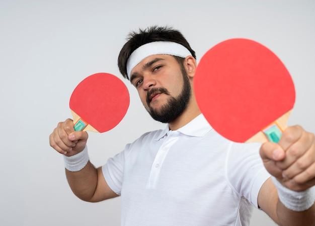 Confiant jeune homme sportif portant bandeau et bracelet tenant des raquettes de ping-pong isolé sur mur blanc