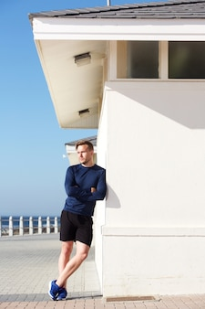 Confiant jeune homme sportif s'appuyant sur le mur extérieur
