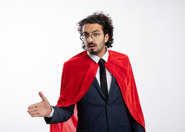 Confiant jeune homme de super-héros caucasien dans des lunettes optiques portant un costume avec une cape rouge tend la main en regardant la caméra