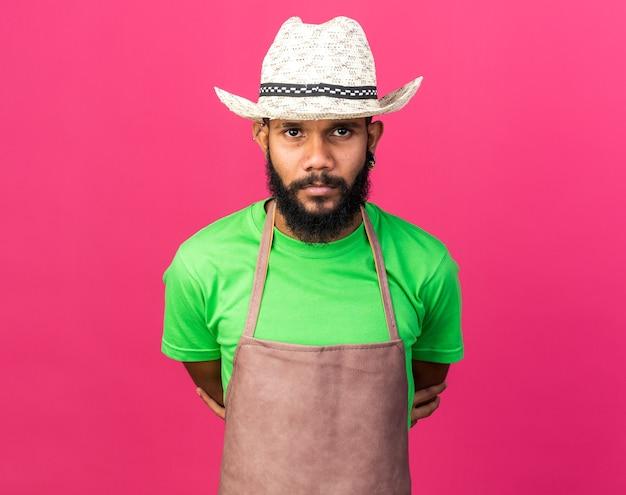 Confiant jeune jardinier afro-américain portant un chapeau de jardinage isolé sur un mur rose