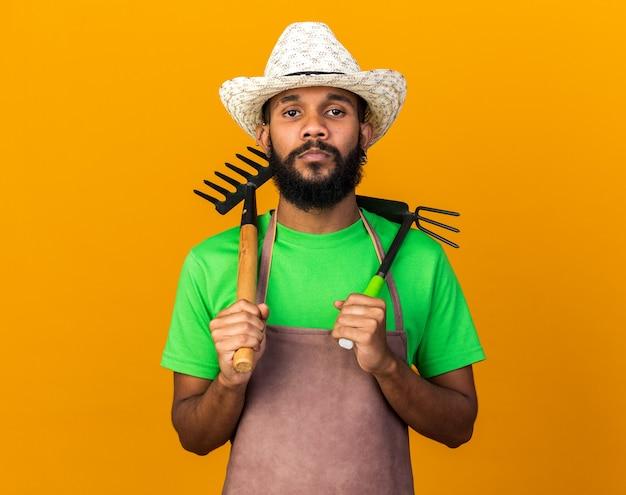 Confiant jeune jardinier afro-américain portant un chapeau de jardinage tenant un râteau avec un râteau de houe sur l'épaule