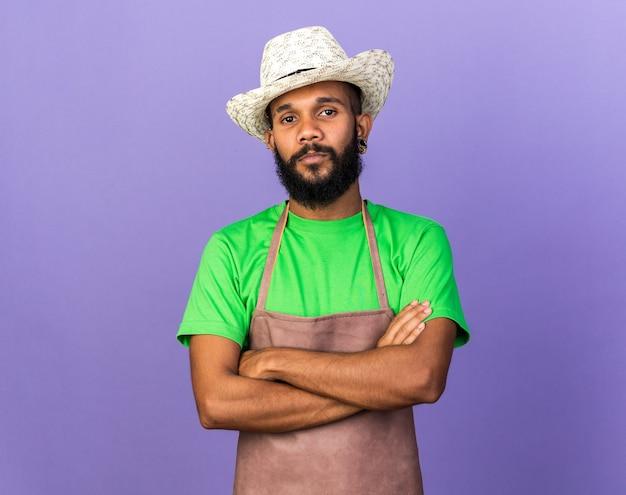 Confiant jeune jardinier afro-américain portant un chapeau de jardinage traversant les mains isolées sur le mur bleu