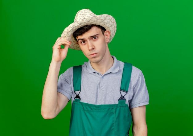 Confiant jeune jardinier mâle portant et tenant un chapeau de jardinage isolé sur fond vert avec espace copie