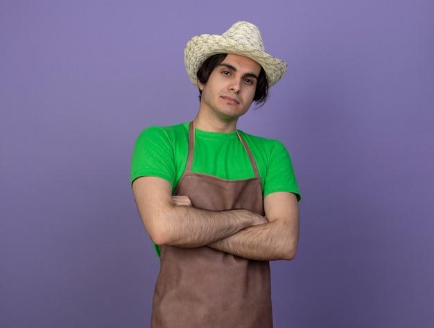 Confiant jeune jardinier mâle en uniforme portant chapeau de jardinage croisant les mains