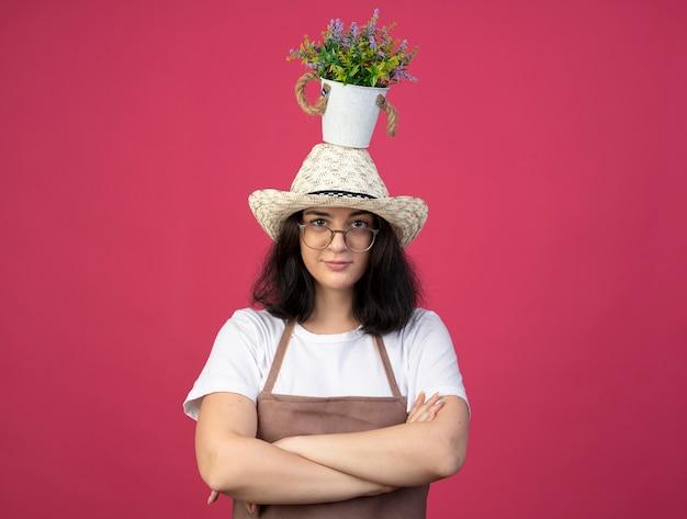 Confiant jeune jardinière brune à lunettes optiques et en uniforme portant un chapeau de jardinage se tient avec les bras croisés tenant un pot de fleurs sur la tête isolé sur un mur rose