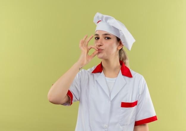 Confiant jeune joli cuisinier en uniforme de chef faisant un geste savoureux isolé sur mur vert