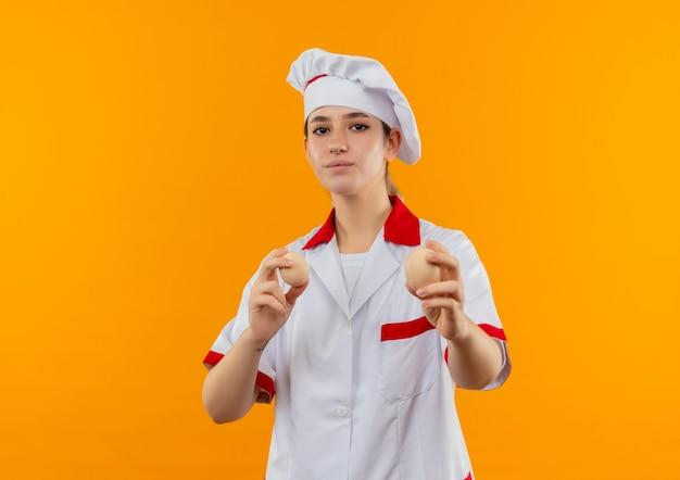 Confiant jeune joli cuisinier en uniforme de chef tenant et étirant des œufs isolés sur un mur orange avec espace de copie