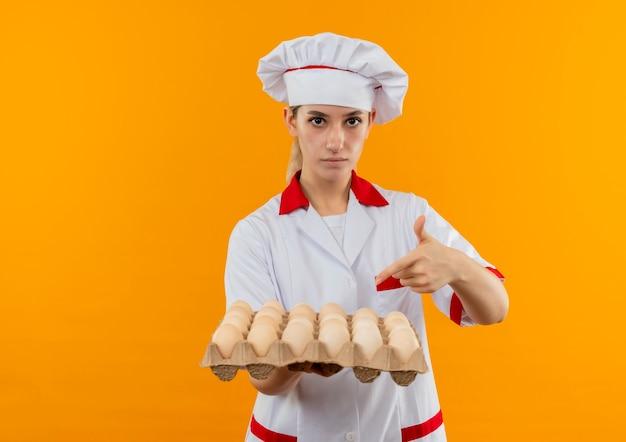 Confiant jeune joli cuisinier en uniforme de chef tenant et pointant sur un carton d'œufs isolé sur un mur orange avec espace de copie