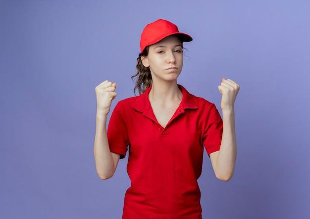 Confiant jeune jolie femme de livraison portant l'uniforme rouge et le chapeau levant les poings