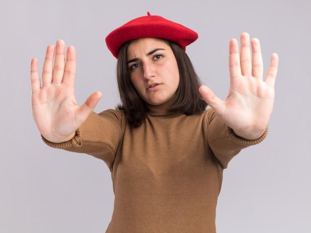 Confiant jeune jolie fille caucasienne avec un chapeau de béret gesticulant un panneau d'arrêt à deux mains