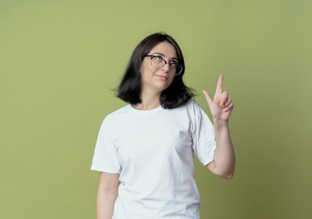 Confiant jeune jolie fille caucasienne portant des lunettes en levant et faisant le geste de perdant isolé sur fond vert olive avec espace de copie