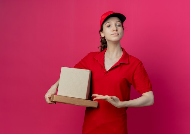 Confiant jeune jolie livreuse portant un uniforme rouge et une casquette tenant et pointant avec la main à la boîte en carton et paquet de pizza isolé sur fond cramoisi avec espace copie