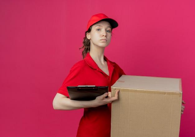Confiant jeune jolie livreuse en uniforme rouge et cap holding boîte en carton et presse-papiers isolé sur fond cramoisi avec espace de copie