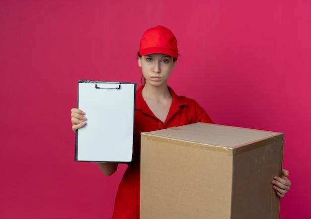 Confiant jeune jolie livreuse en uniforme rouge et cap tenant la boîte en carton et montrant le presse-papiers isolé sur fond cramoisi avec espace de copie