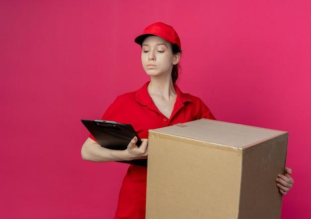 Confiant jeune jolie livreuse en uniforme rouge et cap tenant la boîte en carton et le presse-papiers en regardant le presse-papiers isolé sur fond cramoisi avec espace de copie