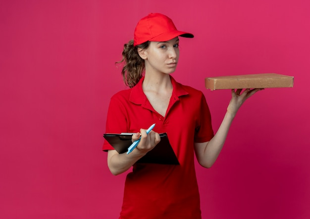 Confiant jeune jolie livreuse en uniforme rouge et cap tenant le stylo de paquet de pizza et presse-papiers isolé sur fond cramoisi avec espace de copie