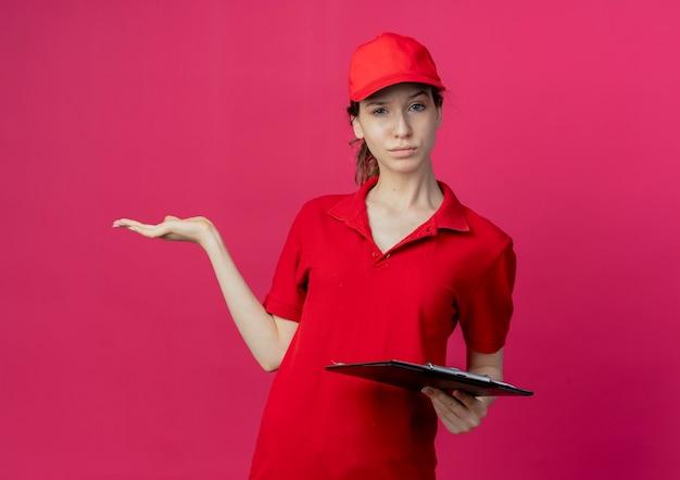 Confiant jeune jolie livreuse en uniforme rouge et chapeau tenant le presse-papiers et montrant la main vide isolée sur fond cramoisi avec espace de copie