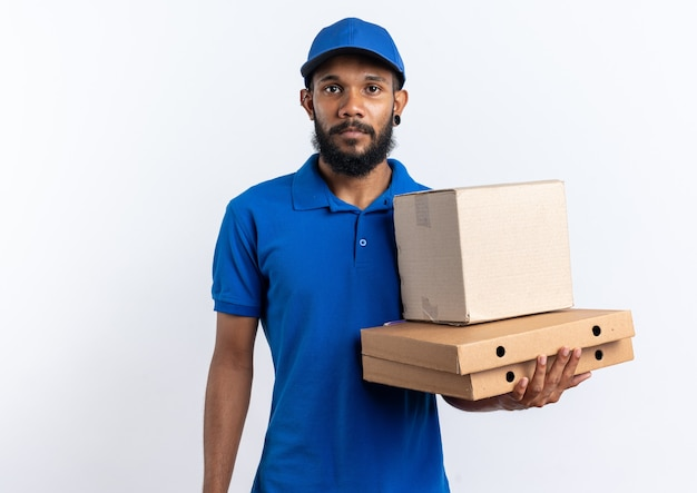 Confiant jeune livreur afro-américain tenant une boîte en carton sur des boîtes à pizza isolées sur un mur blanc avec espace de copie