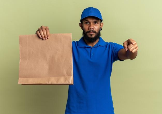 Confiant jeune livreur afro-américain tenant un paquet de nourriture et pointant isolé sur un mur vert olive avec espace de copie